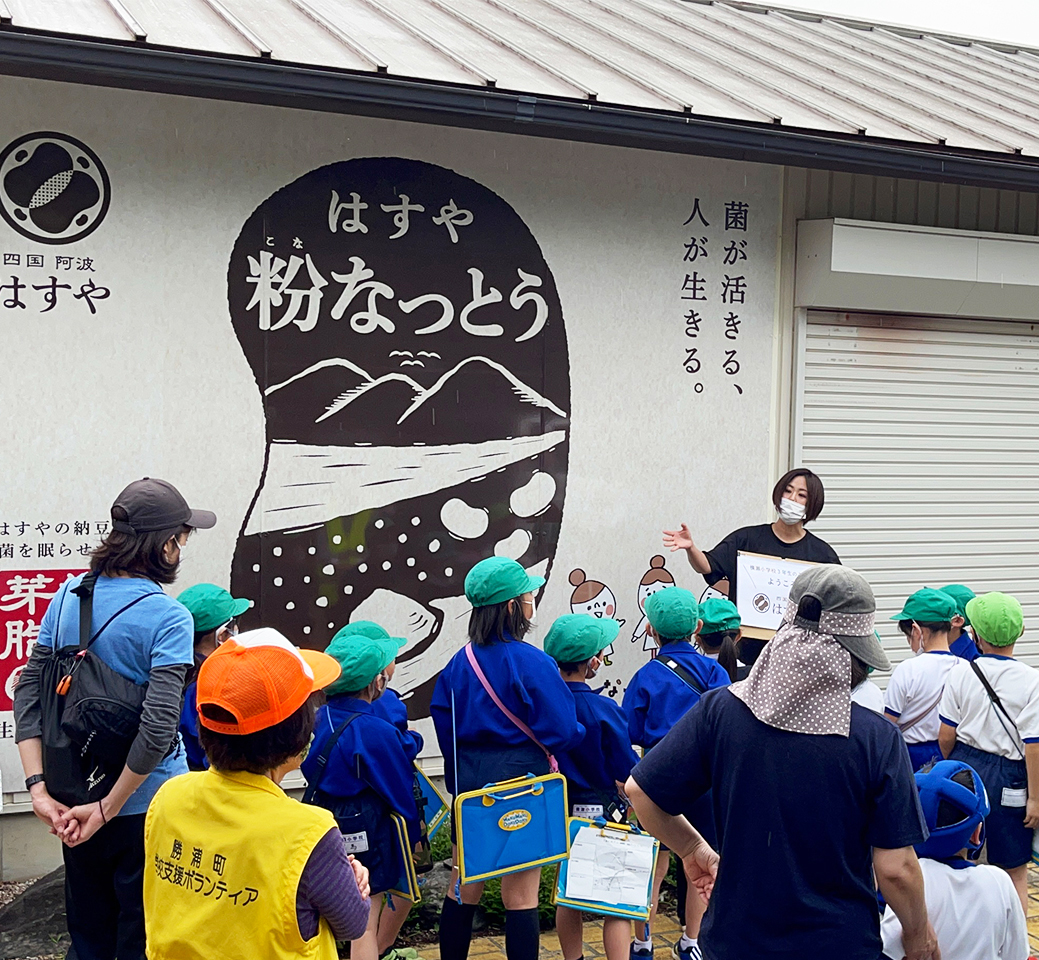 四国阿波はすやの看板の前で工房見学に来た小学生に説明をするはすやのスタッフ